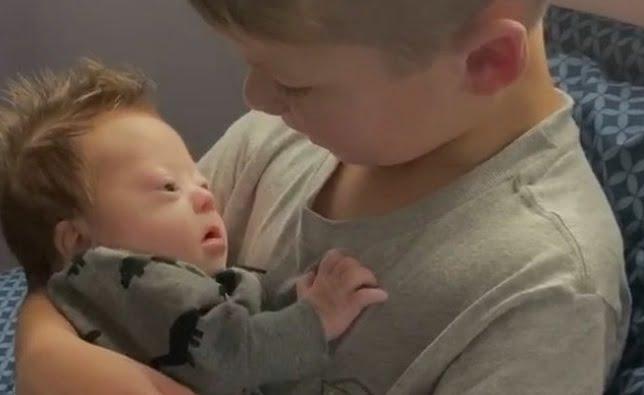 Bebelus cu sindromul Down, tinut in brate de fratele mai mare | Demamici.ro