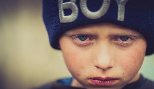 Un copil din Botoșani, cu ochii în lacrimi. A rămas desculț, fără adidași, după incendiul care a distrus casa familiei