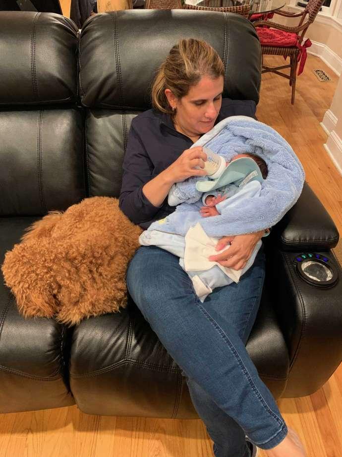 O profesoară are grijă de frățiorul nou născut al elevei sale, în timp ce familia se tratează de COVID-19